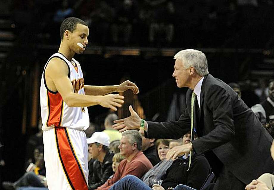 Golden State Warriors' Stephen Curry reaches to shake hands and hug former coach, Davidson's Bob McKillop, prior to tipoff of the Warriors' game against the Charlotte Bobcats at Time Warner Cable Arena in Charlotte, North Carolina, on Saturday, March 6, 2010. (David T. Foster III/Charlotte Observer/MCT) Photo: David T. Foster Iii, MCT