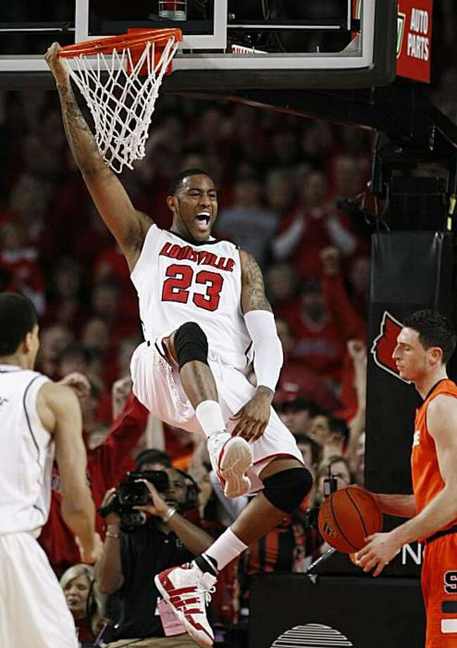 Louisville's Terrence Jennings hangs on the rim after dunking the ball during the first half of their NCAA college basketball game against Syracuse in Louisville, Ky., Saturday, March 6, 2010. Photo: Ed Reinke, AP