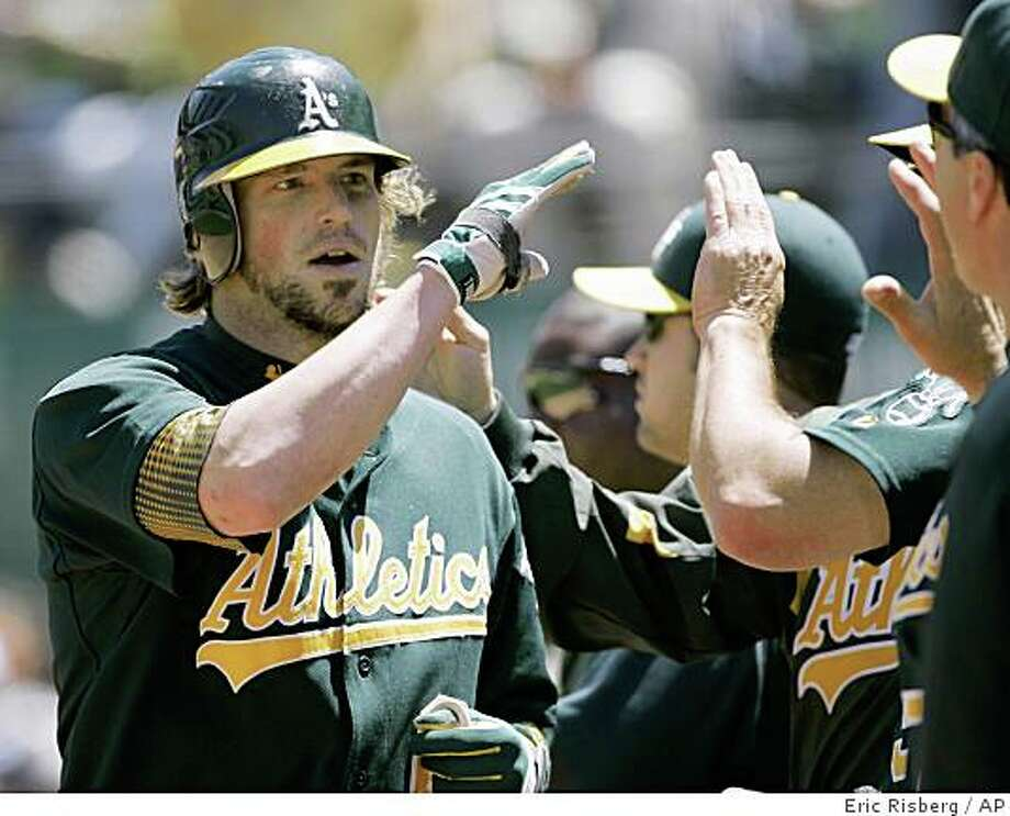 Oakland Athletics' Travis Buck is greeted by his teammates in the dugout after hitting a home run off Detroit Tigers starting pitcher Nate Robertson during the sixth inning of a baseball game in Oakland, Calif., Wednesday, June 4, 2008. Oakland won 10-2, to sweep the three-game series. (AP Photo/Eric Risberg) Photo: Eric Risberg, AP