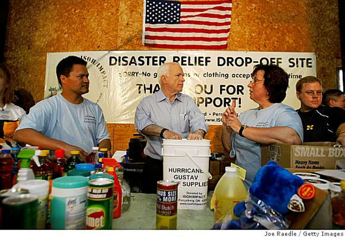 WATERVILLE, OH - SEPTEMBER 1: Presumptive Republican presidential nominee John McCain (R-AZ) speaks with Linda Greene, president and CEO of ISOH/IMPACT, a non-profit organization that is collecting relief supplies for victims of Hurricane Gustav September 1, 2008 in Waterville, Ohio. The Republican National Convention, which runs September 1-4 in St. Paul, Minnesota, has cancelled much of its program for the first day due to the storm. (Photo by Joe Raedle/Getty Images)