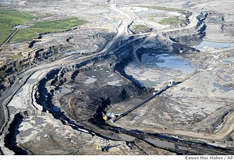 ** ADVANCE FOR SUNDAY, AUG. 24 ** This June 25, 2008 photo shows an aerial view just north of Fort McMurray in Alberta, Canada, where the world's largest oil companies are building massive open pit mines to get at the oil sands. Plans have been made to strip and excavate an area in northern Alberta that's the size of New York state. The region could yield as much as 175 billion barrels of oil. Daily production of 1.2 million barrels from the oil sands is expected to nearly triple to 3.5 million barrels in 2020. Overall, Alberta has more oil than Venezuela, Russia or Iran. Only Saudi Arabia has more. (AP Photo/Eamon Mac Mahon) ** NO ARCHIVE ** Photo: Eamon Mac Mahon, AP