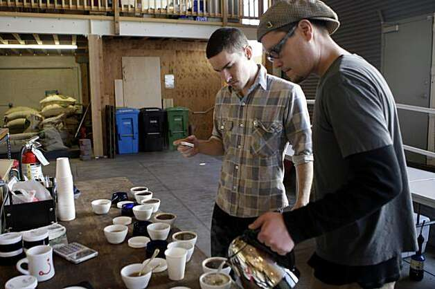 Brandon McMahon, assistant wholesale manager Ritual Coffee Roasters, starts a timer while Joel Edwards, Ritual Coffee Roasters production roaster, starts pouring hot water over ground coffee as they prepare for a cupping at Ritual Coffee Roasters.  The cupping is a quality control measure. Photo: Lea Suzuki, The Chronicle