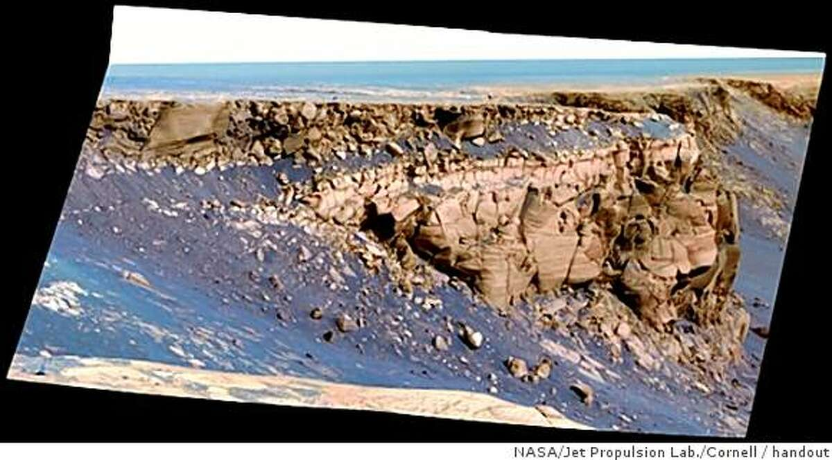 """This image captured by NASA's Mars Exploration Rover Opportunity shows """"Cape St. Vincent,"""" one of the many promontories that jut out from the walls of Victoria Crater, Mars. The material at the top of the promontory consists of loose, jumbled rock, then a bit further down into the crater, abruptly transitions to solid bedrock. This transition point is marked by a bright band of rock, visible around the entire crater."""