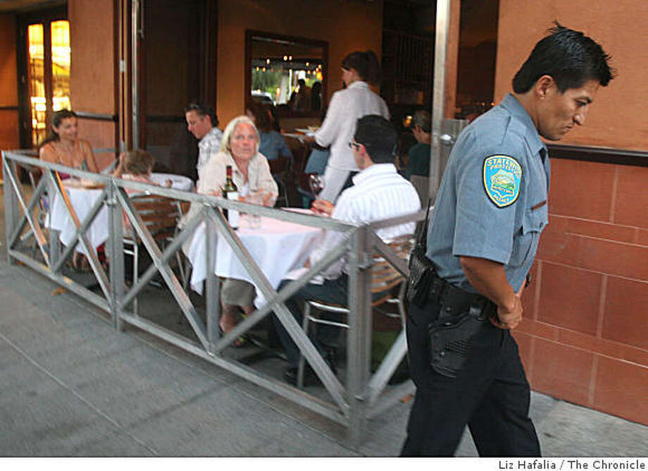 Adan Bernardino passes the outside patio at Oliveto, the corner restaurant at Market Hall, while patrolling in the Rockridge area of Oakland, Calif., on Thursday night, August 28, 2008. Photo: Liz Hafalia, The Chronicle