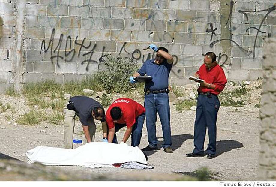 Forensic officers cover the body of a man gunned down during a shooting between rival drug gangs at a neighbourhood on the outskirts of the border city of Ciudad Juarez August 21, 2008. More than 2,000 people have died this year in Mexico's drug war, mostly between rival gangs, in a fight for control of smuggling corridors into the United States. Ciudad Juarez, across the border from El Paso, Texas, has the highest murder toll of the country this year, with 867 killed, according to media. Picture taken August 21, 2008. REUTERS/Tomas Bravo (MEXICO) Photo: Tomas Bravo, Reuters