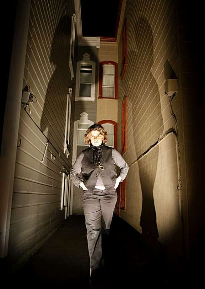 Bay Area artist/light designer Elaine Buckholtz stands between two of the volunteer homes that allowed her to light them as part of The Urban Unseen project sponsored by USF. Thursday Feb. 25, 2010 the event took place in San Francisco in the 1900 block of Golden Gate Avenue. Photo: Lance Iversen, The Chronicle