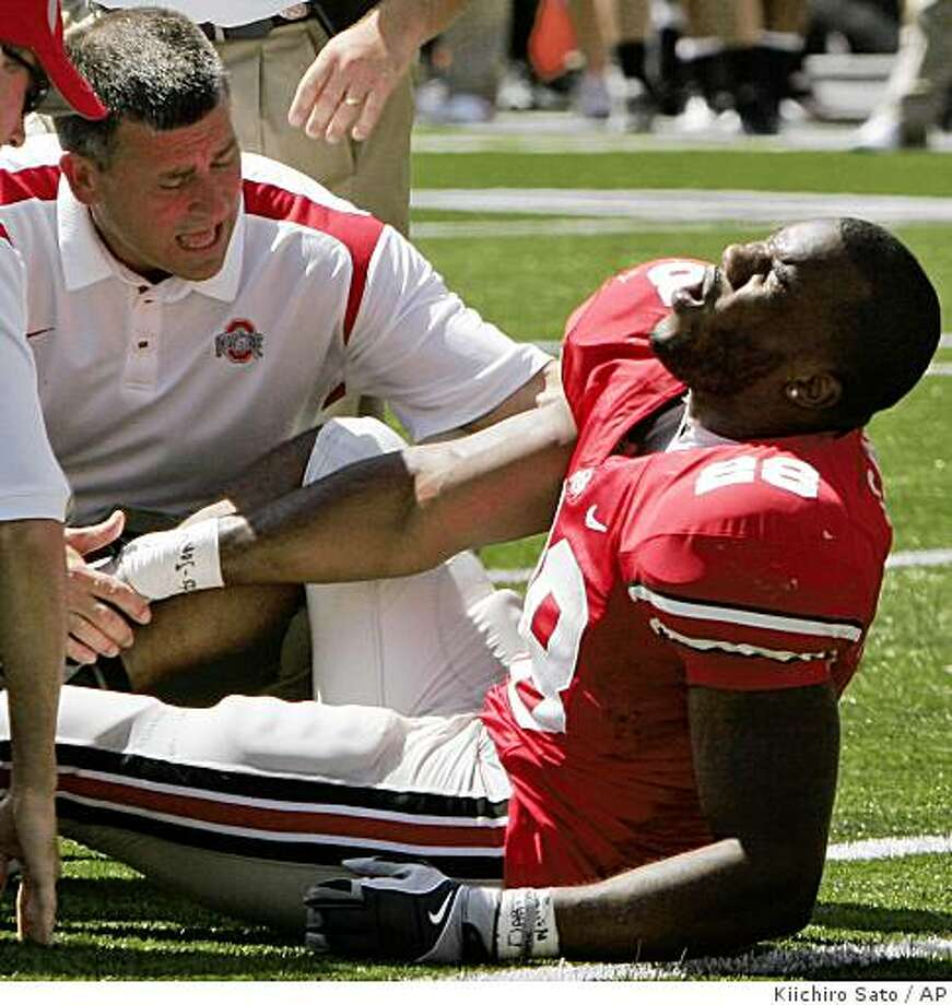 Ohio State running back Chris Wells reacts as trainers check on his injury during the third quarter of a college football game against Youngstown State, Saturday, Aug. 30, 2008 in Columbus, Ohio.  (AP Photo/Kiichiro Sato) Photo: Kiichiro Sato, AP