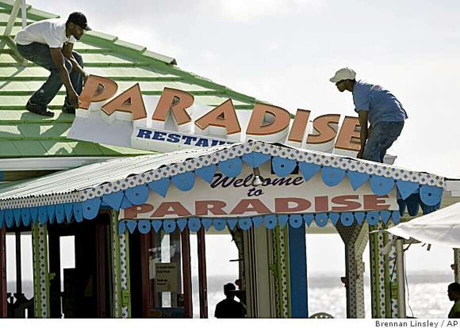 Workers remove a roof sign from Paradise Restaurant in preparation for the arrival of the Gustav storm system in George Town on Grand Cayman Island, Thursday, Aug. 28, 2008. Gustav surged toward renewed hurricane force on Thursday as it drove toward Jamaica, while many miles away, New Orleans watched it with a nervous eye. (AP Photo/Brennan Linsley) Photo: Brennan Linsley, AP