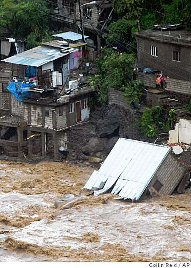 A home is seen fallen into a swollen river caused by Tropical Storm Gustav in Kingston, Jamaica, Fri., Aug 29, 2008.  Deadly Gustav drenched Jamaica and menaced the Cayman Islands on Friday, and on the anniversary of Hurricane Katrina's landfall, forecasters said for the first time there's a better-than-even chance that New Orleans will get slammed by tropical storm-force winds. (AP Photo/Collin Reid) Photo: Collin Reid, AP