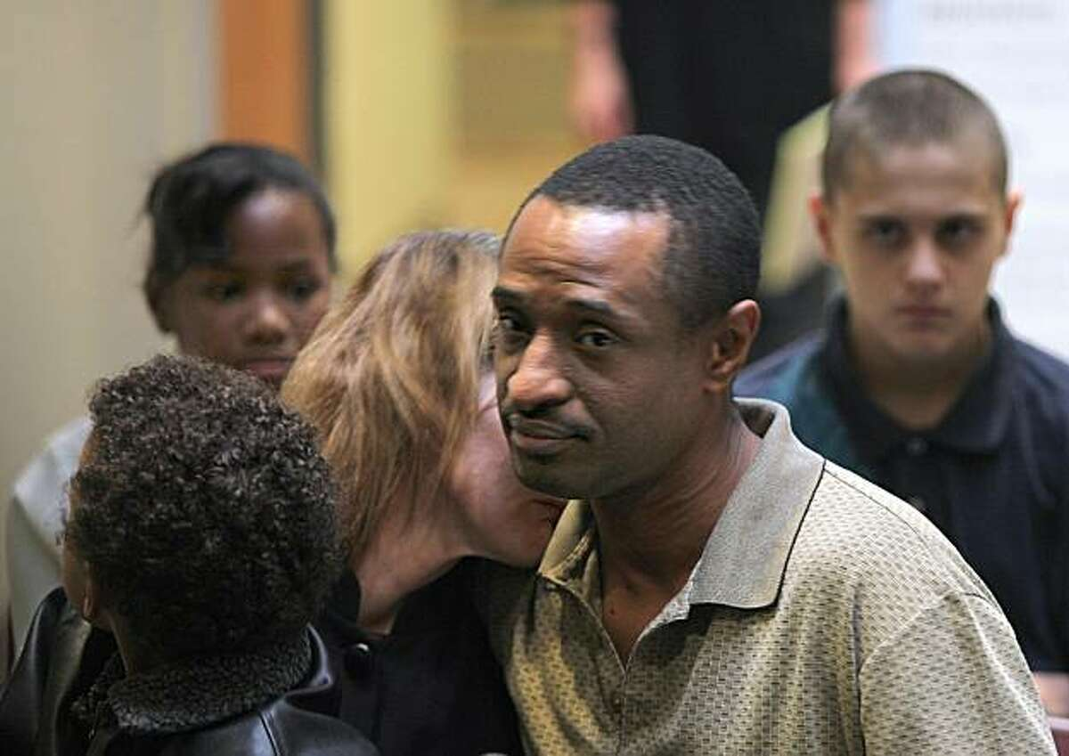 Charles Washington, right, talks on behalf of his family at the Asian Law Caucus office in San Francisco on Monday. His wife, Tracey Washington, left, and their 13-year-old and 5-year-old sons are being deported this week. The 13-year-old, back right, has a hearing next week for hitting another boy and stealing 46 cents. At back left is Charles' 12-year-old daughter.