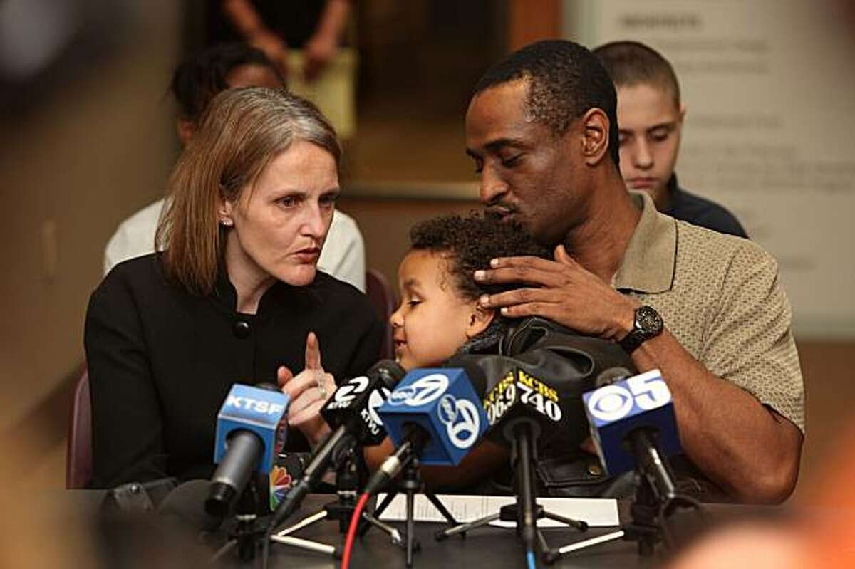 Charles Washington, right, talks on behalf of his family at the Asian Law Caucus office in San Francisco on Monday. His wife, Tracey Washington, left, and their sons are being deported this week.