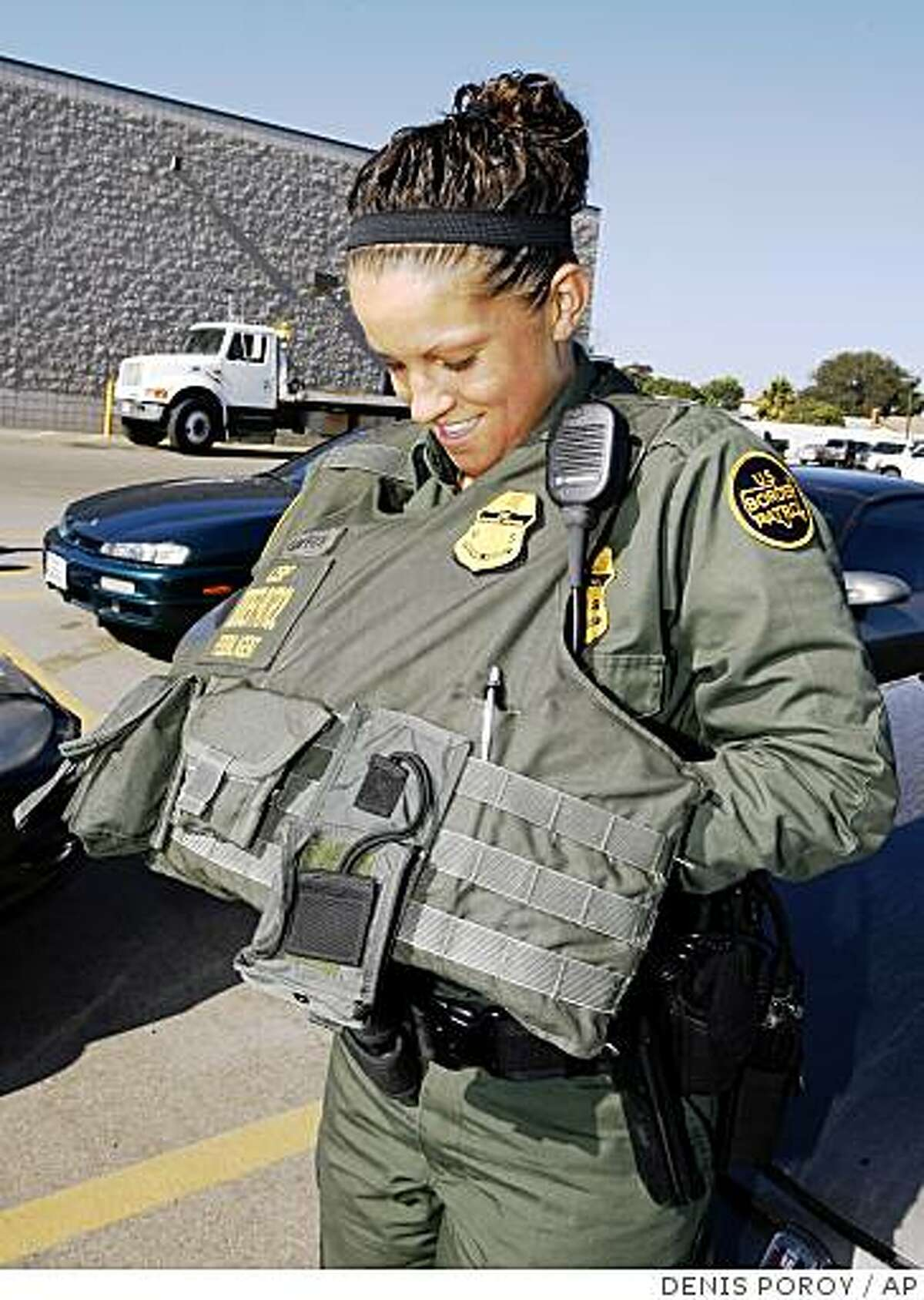U.S. Border Patrol agent Kate Griffith puts on her bullet-proof vest at the start of her shift at the Imperial Beach Border Patrol Station Wednesday, Aug. 6, 2008 in Imperial Beach, Calif. Griffith has been a border patrol agent for little over 20 months.The sobering reality of life on the border has created an environment in which about 30 percent of agents leave the agency in less than 18 months. (AP Photo/Denis Poroy)