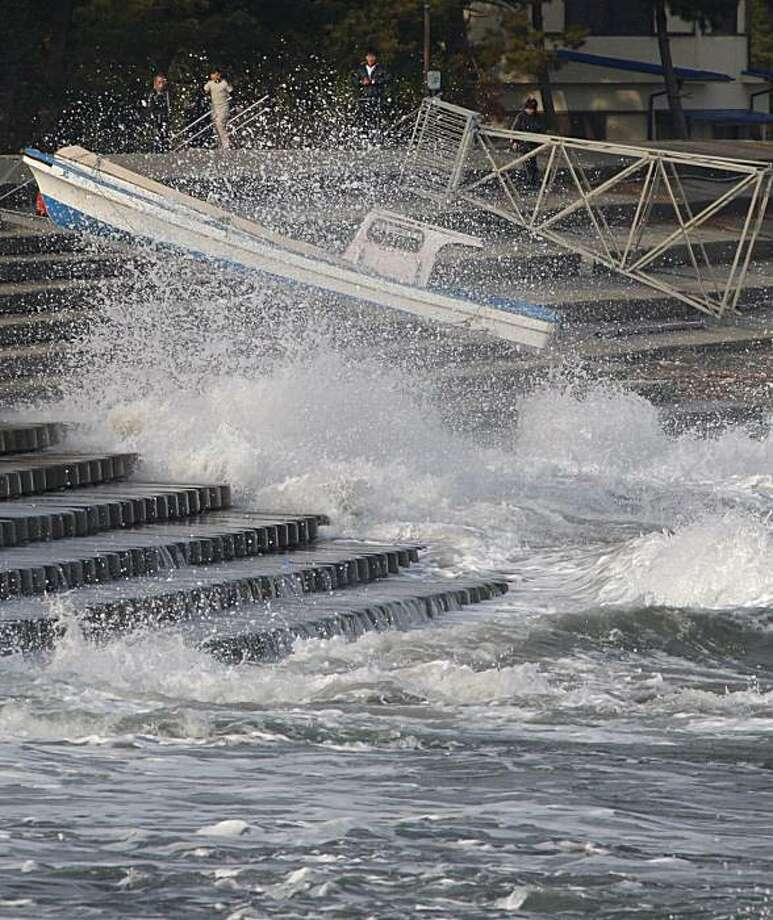 Local residents in Shichigahama, Miyagi Prefecture (state), northern Japan, look at a wave washing stairs built on the shore at a fishing port Sunday, Feb. 28, 2010. The tsunami hit Japan's main islands on Sunday, but the initial waves washed ashore without causing any damage after sparing most of the Pacific islands that were in its path. Photo: Shuji Kajiyama, AP