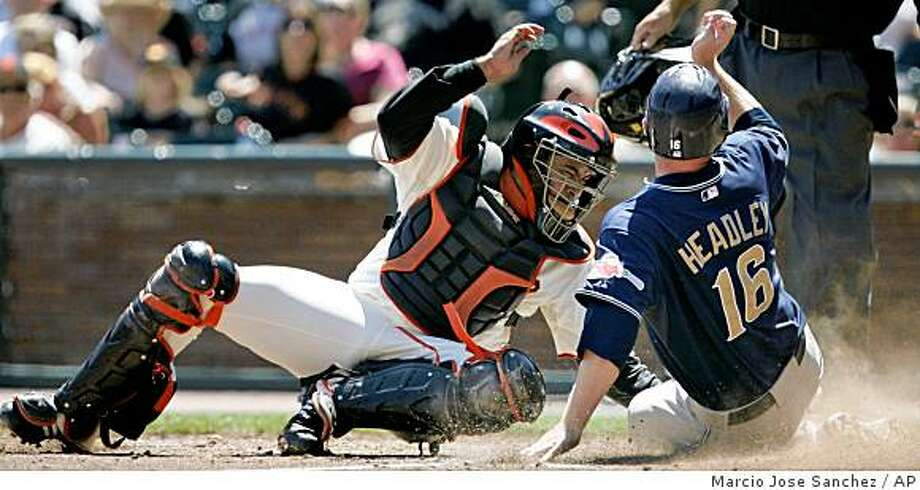 San Diego Padres' Chase Headley, right, slides safely at home plate past the tag-attempt by San Francisco Giants catcher Bengie Molina, left, on a single by Padres' Nick Hundley in the fourth inning of a baseball game in San Francisco, Sunday, Aug. 24, 2008. (AP Photo/Marcio Jose Sanchez) Photo: Marcio Jose Sanchez, AP