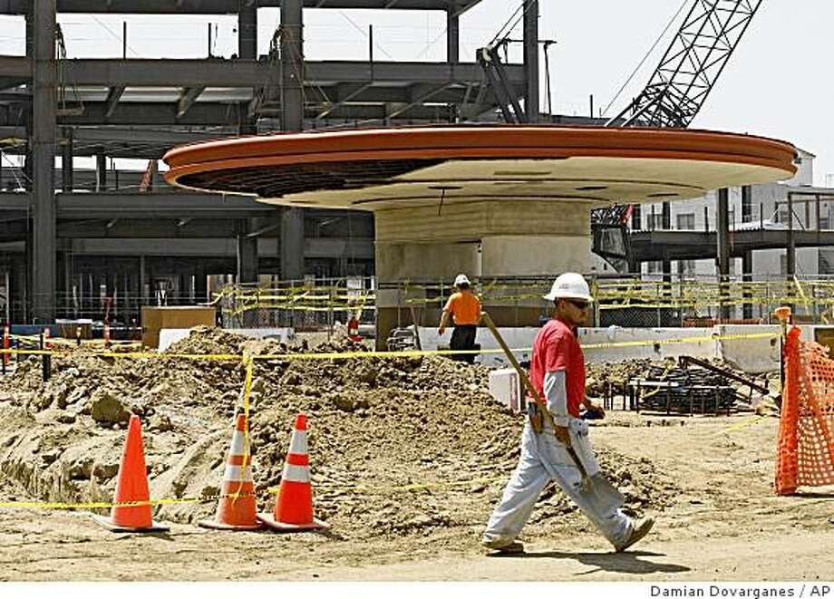 "Workers walk by the entrance of the former Ambassador Hotel which is being preserved alongside the new construction at the site where city officials broke ground Wednesday on a small urban ""pocket park"" at the site where Robert F. Kennedy was assassinated 40 years ago, Wednesday, Aug. 27, 2008 in Los Angeles. (AP Photo/Damian Dovarganes) Photo: Damian Dovarganes, AP"