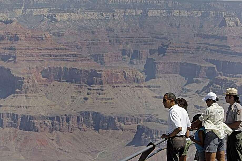 FILE - In this 2009, Aug. 16, file photo, President Barack Obama, his wife Michelle Obama, and daughters Malia Obama, 11, Sasha Obama, 8, with Interpretive Park Ranger Scott Kraynak look out over Hopi Point as they tour the Grand Canyon in Grand Canyon National Park, Ariz. Ten million more people visited national parks last year than in 2008, according to final statistics from the National Park Service, though the numbers fell short of the all-time record for park visitation from 1987. The agency said onepossible factor in the increase over 2008 may have been publicity from visits last summer by the Obama family to Yellowstone and the Grand Canyon. Photo: Alex Brandon, AP