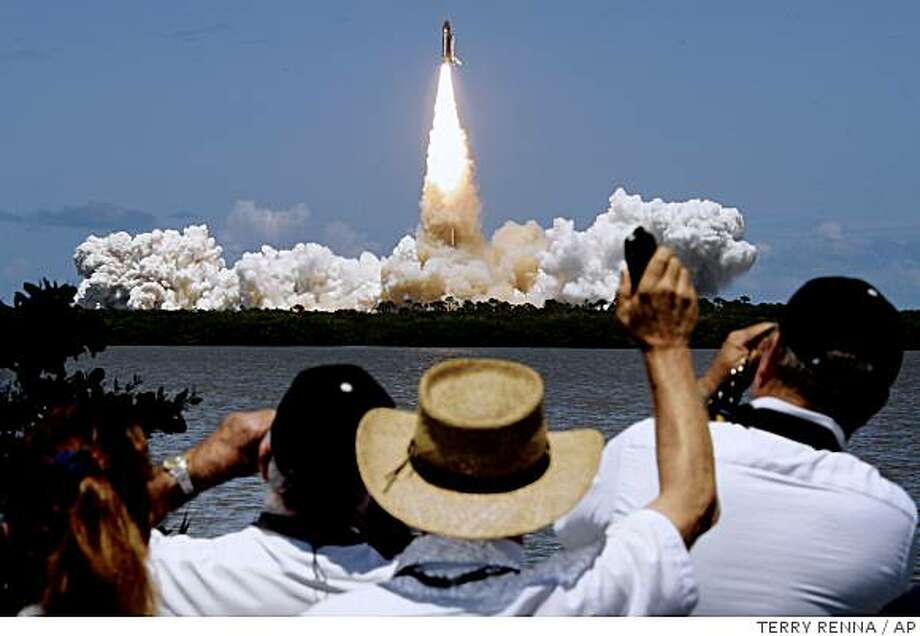 Spectators watch as the space shuttle Discovery lifts off at the Kennedy Space Center in Cape Canaveral, Fla., on mission STS-121 Tuesday, July 4, 2006. Photo: TERRY RENNA, AP