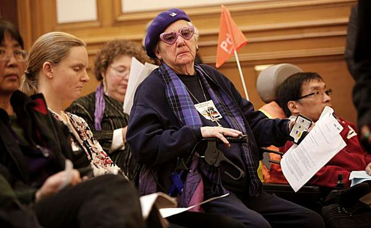 Jeanne Lynch, who has been a Muni rider since 1959, listens to comments during a public meeting of the San Francisco Municipal Transportation Agency in San Francisco on Friday.