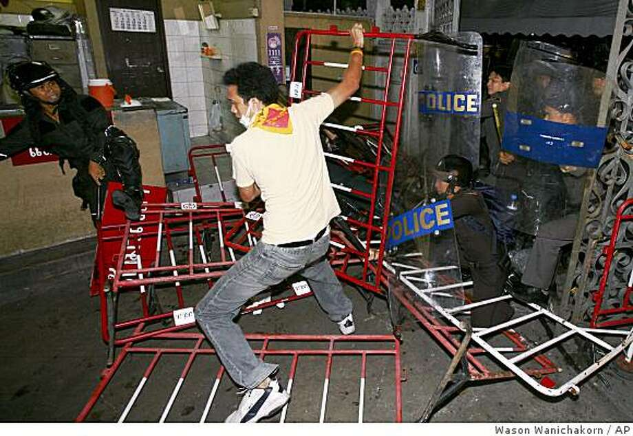 Thai riot police clash with a demonstrator inside the Government House after breaking into the building through a gate, in Bangkok, Thailand, early Wednesday August 27, 2008.  Thousands of anti-government demonstrators had been occupied the Thai prime minister's office compound in a protest to accuse a prime minister too closely tied to his disgraced predecessor. (AP Photo/Wason Wanichakorn) Photo: Wason Wanichakorn, AP