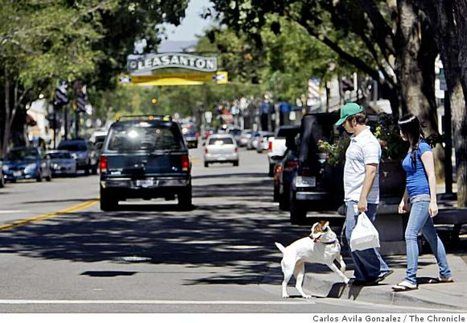 Miles Sanders, center, and Meg Morris, right, walk Jada on Main Street in Pleasanton, Calif., on Tuesday, August 26, 2008, the day the city scored the highest in median income in smaller United States cities in the newest census. Photo: Carlos Avila Gonzalez, The Chronicle