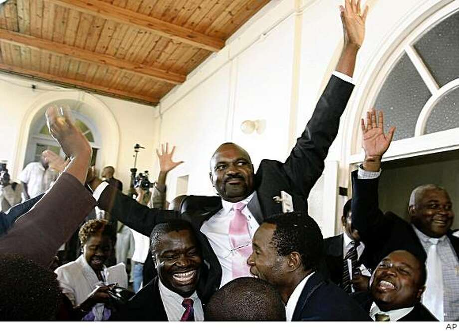 Lovemore Moyo, of the Movement for Democratic Change, center, is lifted up by his party members after being sworn in the newly elected Speaker of Zimbabwe's Parliament in Harare, Monday Aug. 25, 2008. Moyo, won the key position by 110 votes to 98 votes in a major victory for the main opposition party.  Monday's vote came after two opposition politicians were arrested as they entered parliament to be sworn in. President Robert Mugabe was to officially open parliament Tuesday.  (AP Photo) Photo: AP