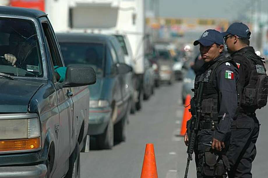 Federal police check vehicles in Ciudad Juarez, Wednesday, Feb. 17, 2010. Mexico's President Felipe Calderon is on a one-day visit to the northern border city terrorized by drug gang violence. Photo: Str, AP