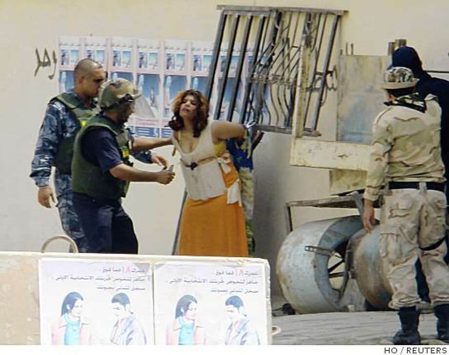 Iraqi police remove a suicide vest from an Iraqi girl in Baquba in this handout photo from the Iraqi police taken August 24, 2008. A teenage Iraqi girl wearing a vest packed with explosives turned herself in rather than go through with a suicide bombing in a violence-torn city north of Baghdad, police and the U.S. military said. REUTERS/Iraqi Police/Handout (IRAQ) Photo: HO, REUTERS