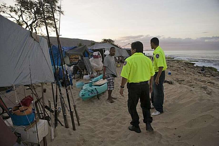 Hawaii Department of Emergency Management officers warn homeless campers of the tsunami warning on Maile Beach, Saturday, Feb. 27, 2010, in Waianae, Hawaii. A tsunami triggered by the Chilean earthquake raced across the Pacific Ocean, threatening Hawaii and the U.S. West Coast as well as hundreds of islands from the bottom of the planet to the top. Sirens blared in Hawaii to alert residents to the impending waves, with authorities asking people living near the water to evacuate. Hawaii Department of Emergency Management officers are combing the beaches warning homeless campers of the danger. Photo: Marco Garcia, AP