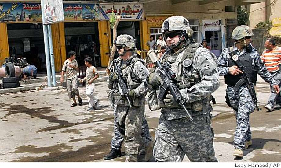 U.S. Army soldiers, center, and Iraqi police, right, provide security during the re-opening of a neighbourhood that had been abandoned by citizens because of sectarian violence, in the Dora area of Baghdad, Iraq, Sunday, Aug. 24, 2008. (AP Photo/Loay Hameed) Photo: Loay Hameed, AP