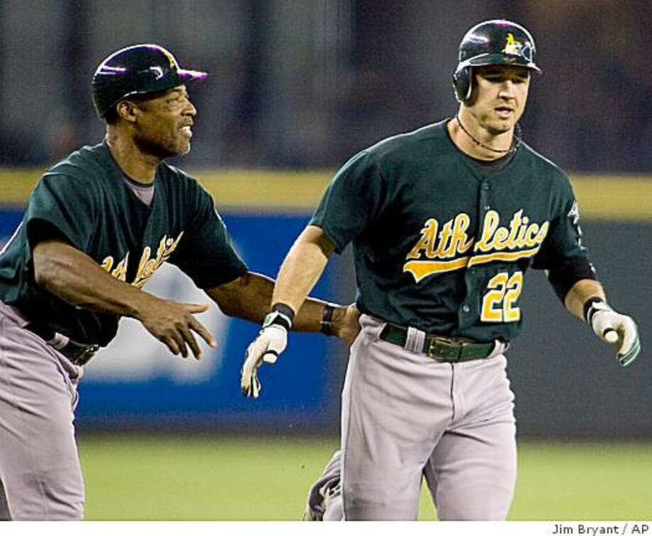 Oakland Athletics' third base coach Tye Young, left, greets Jack Hannahan after he hit a solo home run against the Seattle Mariners in the first inning of baseball game in Seattle on Sunday, Aug. 24, 2008. (AP Photo/Jim Bryant) Photo: Jim Bryant, AP