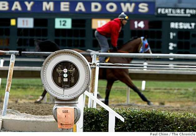 A horse trots on the track behind the scale used to weigh jockeys at the winner's circle at Bay Meadows Race Track in San Mateo, Calif., on Saturday, Aug. 23, 2008. The scale was the first item sold during a three-day auction at the track where horses will continue to train until about October. Photo: Paul Chinn, The Chronicle