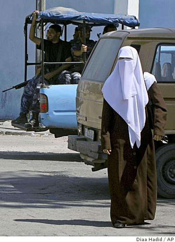 ** ADVANCE FOR SUNDAY, AUG. 24 ** Palestinian police officer Lt. Mariam al-Bursh, one of four women on the drug and vice squad, walks out of the police station in Gaza City, Thursday, Aug. 7, 2008. The 27-year-old lieutenant is one of 53 women serving in the 11,000-strong Hamas police force, established after the Islamic militants seized Gaza by force in June 2007. (AP Photo/Diaa Hadid) Photo: Diaa Hadid, AP
