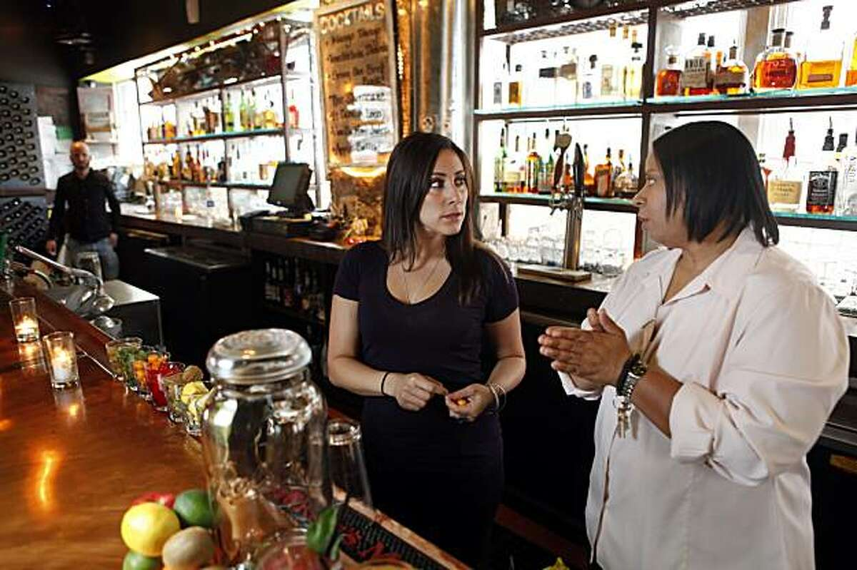 Cassandra Brown, right, manager at Farmer Brown, and Harmony Fraga, left, bar manager, discuss how new recipes for some of their drinks now that thay cannot use house-made infusions. State liquor regulators are cracking down on bars that sell house-made infusions -- taking vodka or gin or other liquors and alcohol and infusing them with fruit or spice. Three San Francisco bars and one in Oakland recently had such infusions confiscated by the ABC. Farmer Brown used to sell infusions, but stopped after hearing about the recent busts.