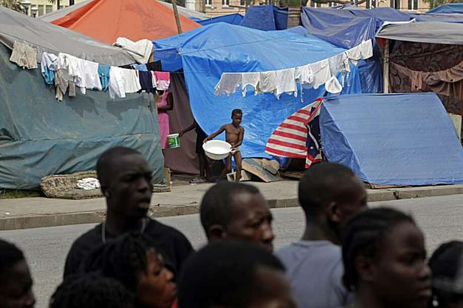 People stand in line to register outside of a camp for home earthquake survivors set up at the main Champ de Mars plaza in Port-au-Prince, Thursday Feb. 25, 2010. The International Organization for Migration began to register thousands at the plaza as relief officials plan to move more than 1.2 million quake victims out of the makeshift camps back to their original neighborhoods. Photo: Ramon Espinosa, AP