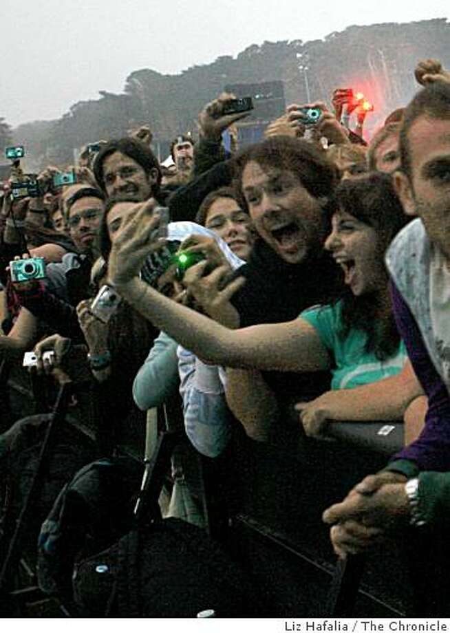 Outside Lands Festival in the first sundown concert at Golden Gate Park while Joe Styers and his girlfriend Tova photograph themselves as Radiohead takes the main stage on the Polo Field in San Francisco, Calif., on Friday, August 22, 2008. Photo: Liz Hafalia, The Chronicle