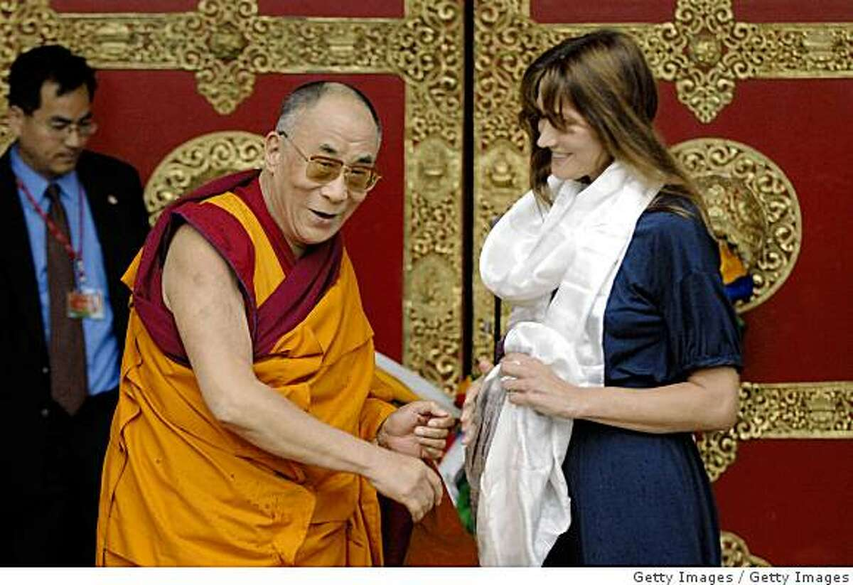 ROQUEREDONDE, FRANCE - AUGUST 22: His Holiness the Dalai Lama (L) and the first lady of France, Carla Bruni-Sarkozy attend the inauguration of Lerab Ling Buddhist temple at Roqueredonde on August 22, 2008 in Languedoc-Roussillon region, southern France. The exiled Tibetan spiritial leader inaugurated and consecrated the temple at the Buddhist retreat during his 12 day visit to France. (Photo by Getty Images)