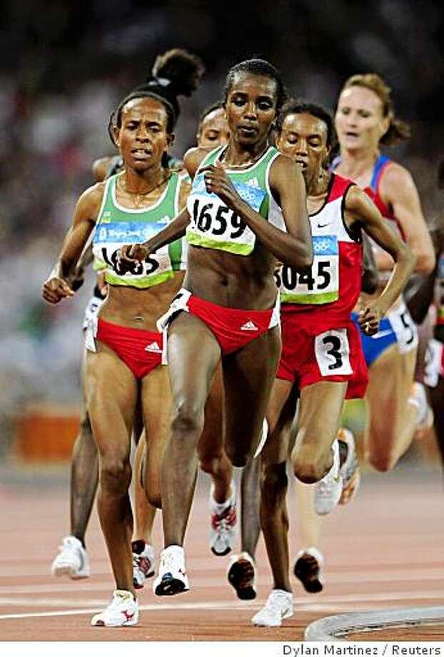 Tirunesh Dibaba of Ethiopia leads the pack on her way to winning the women's 5000m final of the athletics competition in the National Stadium at the Beijing 2008 Olympic Games August 22, 2008. Elvan Abeylegesse (3045) of Turkey finished second Meseret Defar (L) of Ethiopia third. Photo: Dylan Martinez, Reuters
