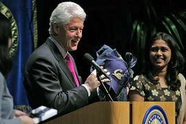"""Former President Bill Clinton is all smiles when he receives some Cal souvenirs after delivering his, """"Global Citizenship: Turning Good Intentions into Positive Action"""" speech to the UC Berkeley community at Zellerbach Hall at the UC Berkeley campus in Berkeley, Calif., on Wednesday, February 24, 2010."""
