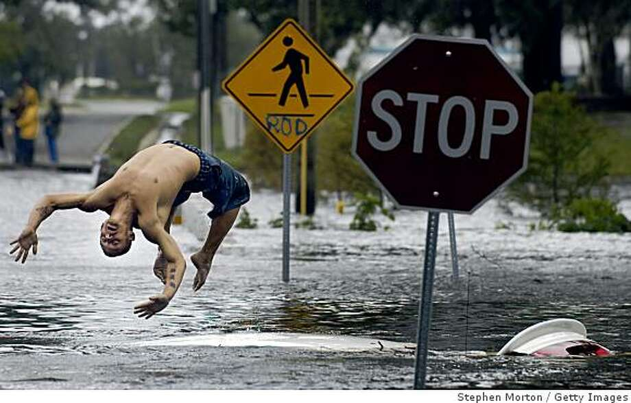 JACKSONVILLE, FL - AUGUST 22: Jason Redden does a back flip off the roof of a submerged car on street near his house during Tropical Storm Fay August 22, 2008 in Jacksonville, Florida. Redden said he rescued the driver after she drove her car through the flooded street. The storm made three separate landfalls and dumped more than two feet of rain in some places. (Photo by Stephen Morton/Getty Images) Photo: Stephen Morton, Getty Images