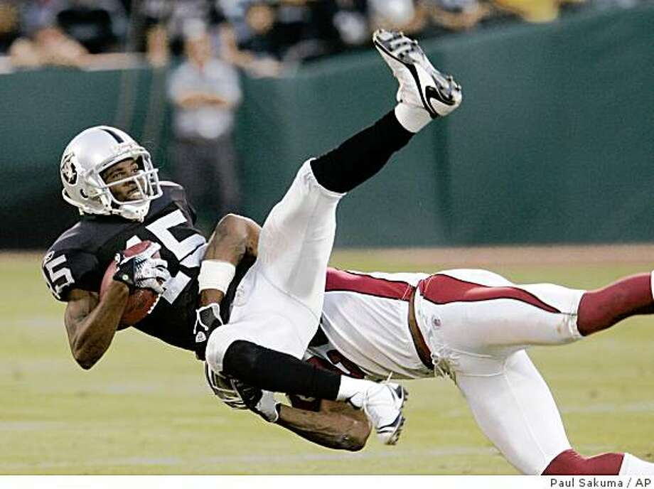 Oakland Raiders wide receiver Johnnie Lee Higgins (15) is tackled by Arizona Cardinals safety Adrian Wilson (24) in the second quarter of their preseason football game in Oakland, Calif., Saturday, Aug. 23, 2008. (AP Photo/Paul Sakuma) Photo: Paul Sakuma, AP