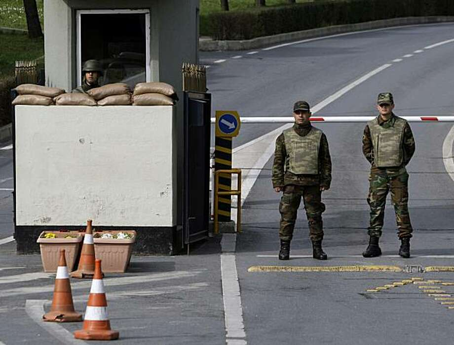 Turkish soldiers stand at the entrance of the War Academy as police search the residence of a retired army commander in Istanbul, Turkey, Monday, Feb. 22, 2010. Turkish police detained about 50 military commanders Monday for allegedly planning to blow upmosques in order to trigger a military takeover and overthrow the Islamic-rooted government. The nationwide sweep highlighted the ongoing struggle between the secular establishment and the Islamic-oriented government _ and left many wondering if the military no longer called the shots in a nation accustomed to viewing it as the pillar of the secular state. Photo: Ibrahim Usta, AP