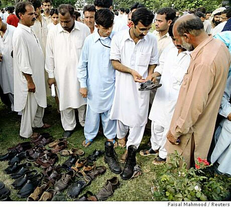 Peoples identify the shoes of their relatives after a suicide attack at a gate of Pakistan's ordinance factory in Wah, a garrison city about 30 km (20 miles) northwest of Islamabad August 21, 2008. Two suicide bombers blew themselves up outside Pakistan's main defence industry complex on Thursday as workers were leaving at the end of their shift, killing nearly 40 people, police said.    REUTERS/Faisal Mahmood   (PAKISTAN) Photo: Faisal Mahmood, Reuters