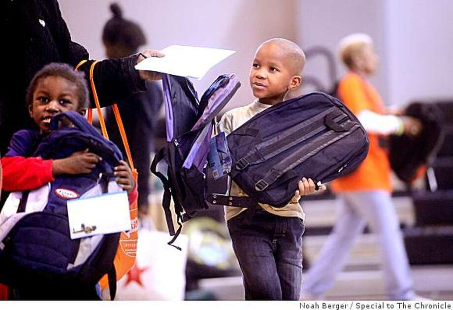 Tommy Harper, 6, carries a backpack he received on Saturday, Aug. 23, 2008, as part of a give-away in San Francisco?s Bayview area. Harper will start first grade at George Washington Carver Elementary School next month. At left is his brother Tony James Harper, 5, who will attend the school as a kindergarten student. Photo: Noah Berger, Special To The Chronicle