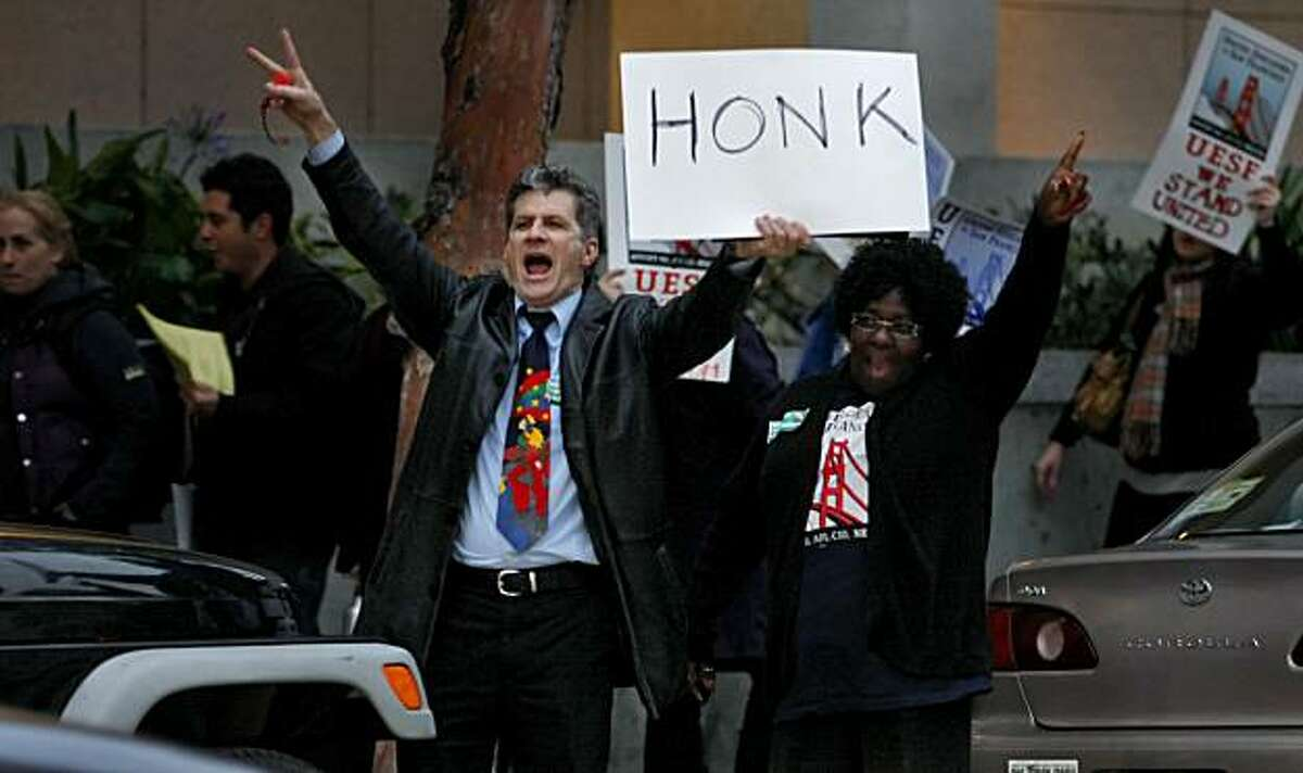 Antonio Mankini and Bobbie Washington yell to commuters to honk in protest of school budget cuts Tuesday in San Francisco.