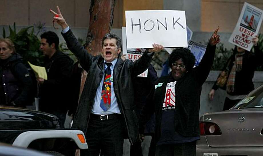 Antonio Mankini and Bobbie Washington yell to commuters to honk in protest of school budget cuts Tuesday in San Francisco. Photo: Lacy Atkins, The Chronicle