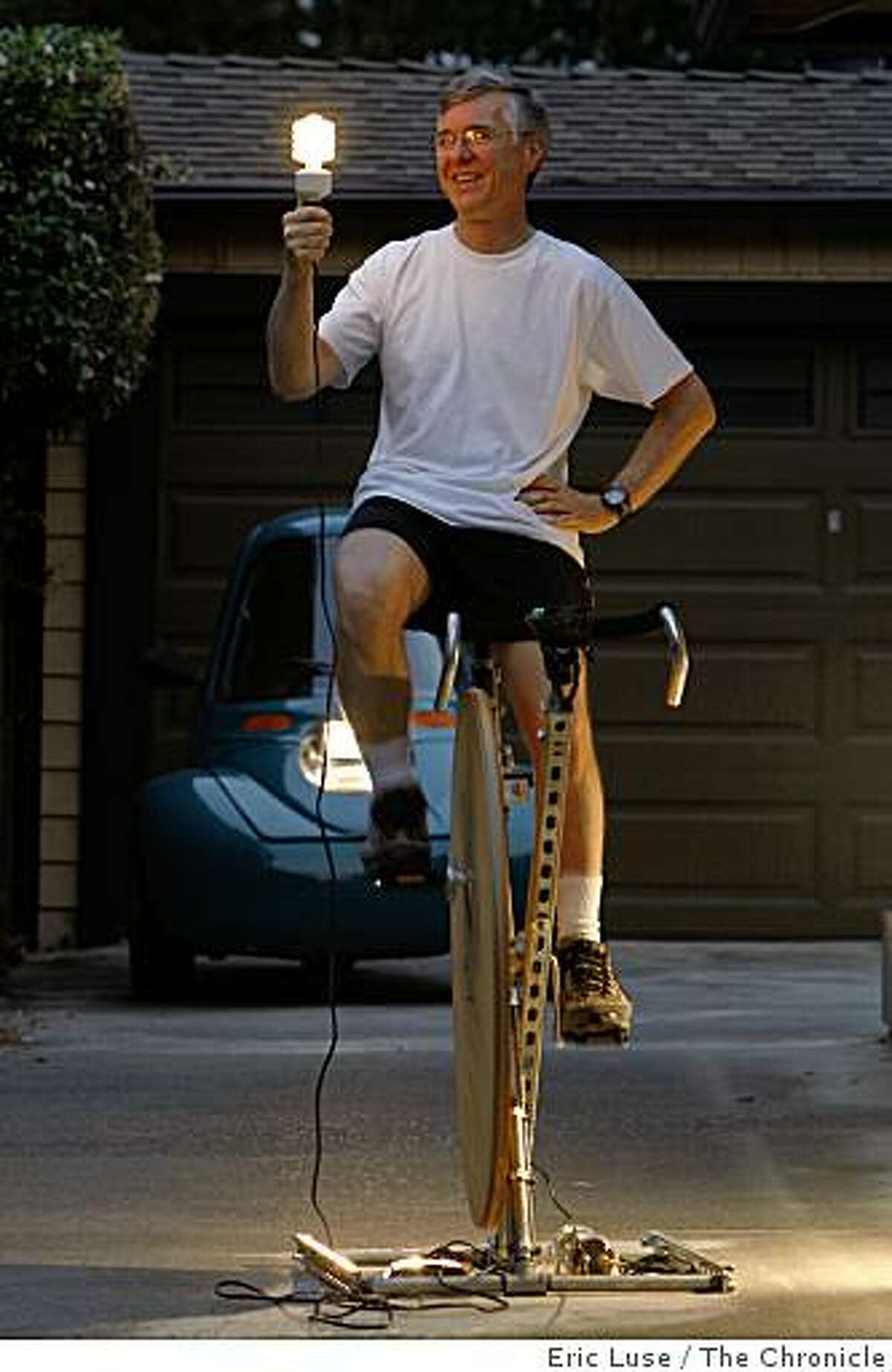 David Butcher holds a light bulb he is generating power for from his PPPM, Pedal Power Prime Mover, at his him in San Jose photographed on Wednesday, June 25, 2008. From the pedal power it goes to a 1.5 Farad Audio Capacitor to an inventor and then lights the bulb.Photo by Eric Luse/ The Chronicle