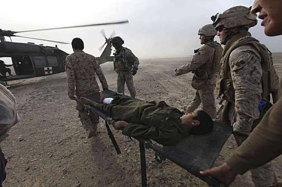U.S. Marines carry an Afghan civilian boy with a gun shot wound to a U.S. Army Task Force Pegasus helicopter during a medevac mission, in  Helmand province, southern Afghanistan, Sunday Feb. 21, 2010. Pegasus crews have come under fire daily while on missions evacuating those wounded as U.S. and Afghan troops take part in the assault in the Taliban-held town of Marjah. Photo: Brennan Linsley, AP