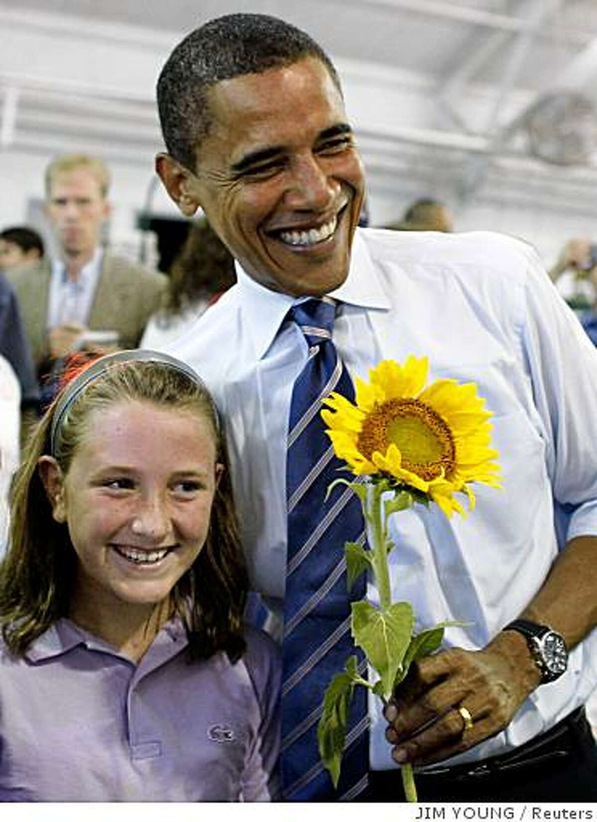 US Democratic presidential candidate Senator Barack Obama (D-IL) holds a sunflower that was given to him during a campaign stop at the Greensboro Farmers Curb Market in Greensboro, North Carolina, August 20, 2008. REUTERS/Jim Young (UNITED STATES) US PRESIDENTIAL ELECTION CAMPAIGN 2008 (USA)