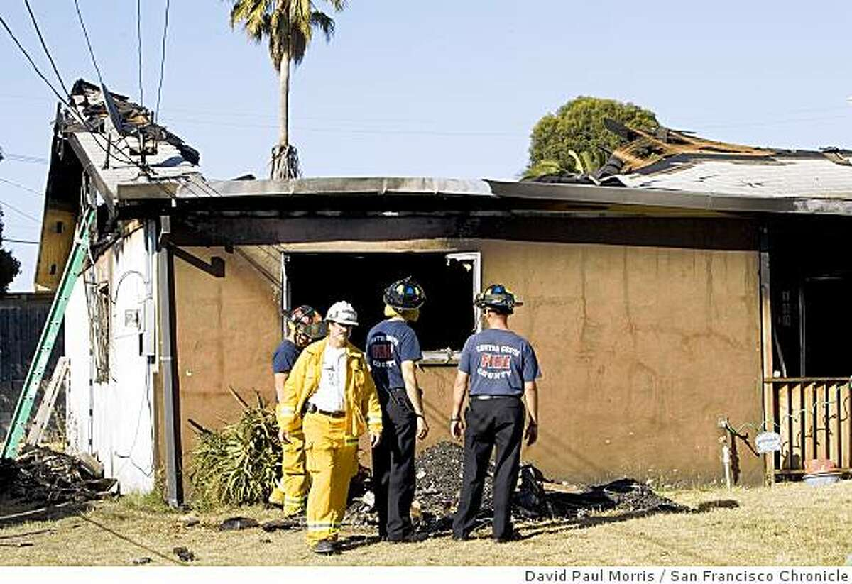 SAN PABLO, CA - JULY 21: Contra Costa County Fire Protection District firefighters look over the roof and debris from a fire that took the lives of two residents and two firefighters on July 21, 2007 in San Pablo, California. The deaths of the firefighters was the first on-duty deaths in the fire district's history, (Photo by David Paul Morris / The Chronicle) Ran on: 07-22-2007