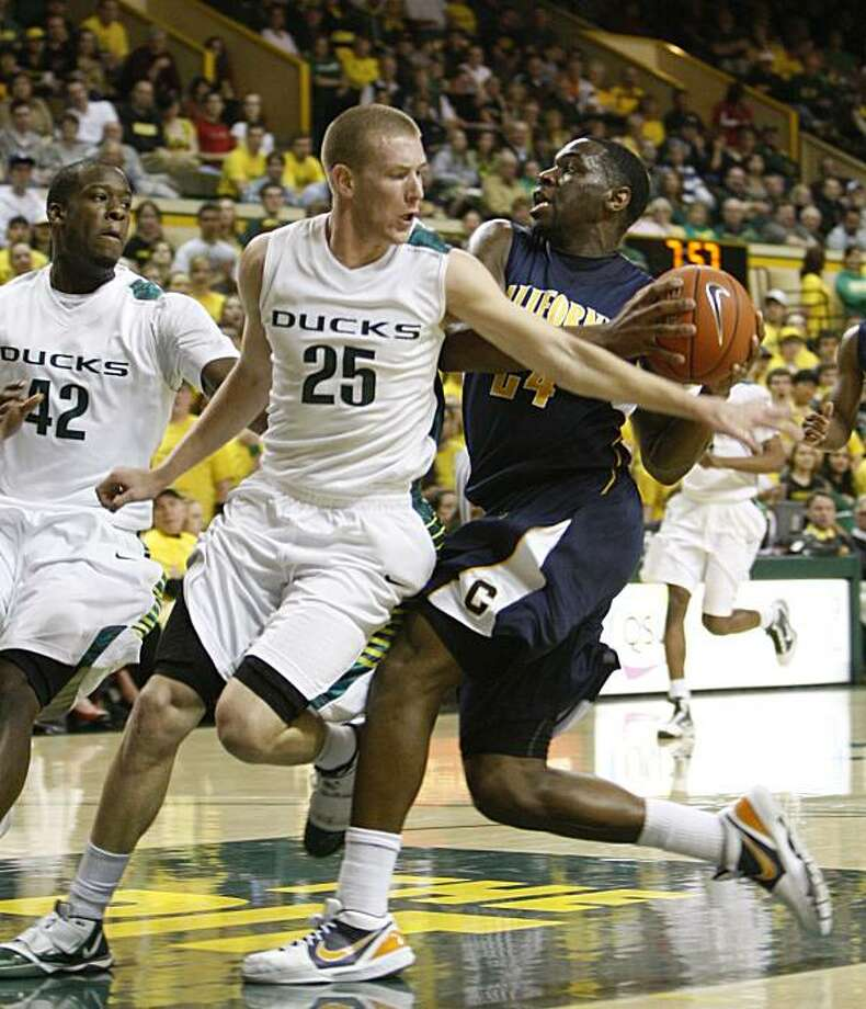 California's Theo Robertson drives to the baskets Oregon's E.J. Singler defends while teammate Josh Crittle looks on in the first half Saturday in Eugene, Ore. Photo: Rick Bowmer, AP